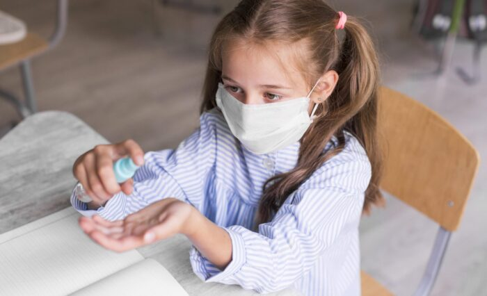 high-angle-kid-disinfecting-her-hands