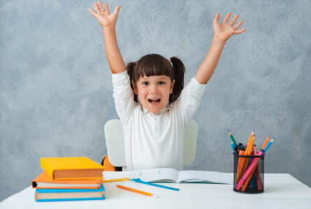 Back to school. Cute child schoolgirl sitting at a Desk in the room. The kid is learning and doing his homework. The girl is emotionally happy with her hands up.